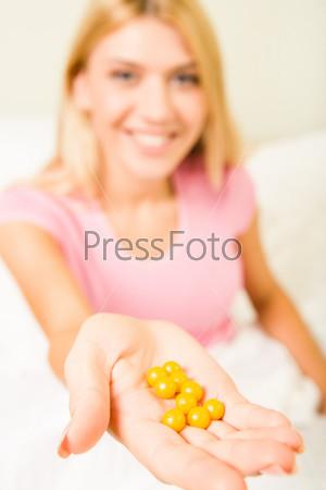 Девушка держит в руке витамины