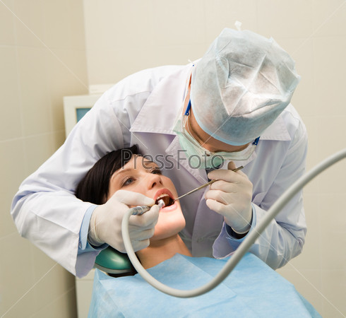 Стоматолог осматривает ротовую полость молодой пациентки
