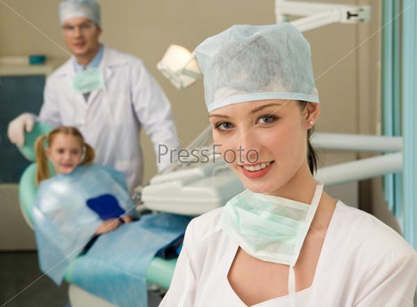 Красивая женщина-стоматолог в белом халате на фоне своего рабочего места