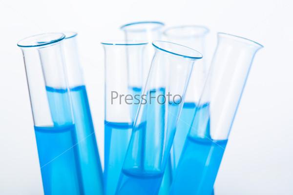 Несколько пробирок с голубой жидкостью на белом фоне