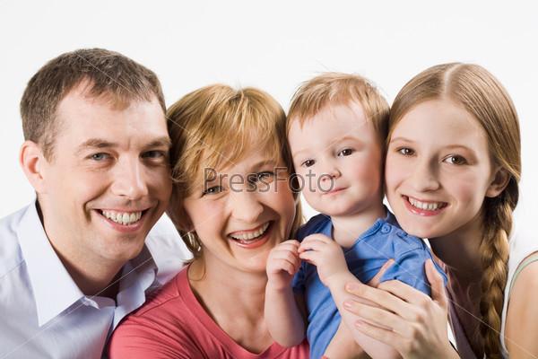 Радостные муж и жена с красивыми детьми смотрят в камеру
