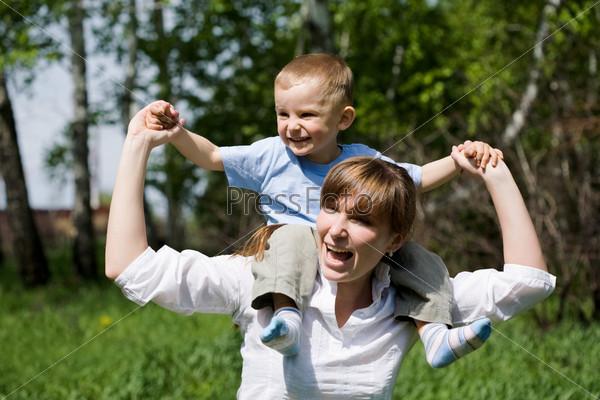 Радостная женщина и игривый ребенок на ее плечах веселятся на природе