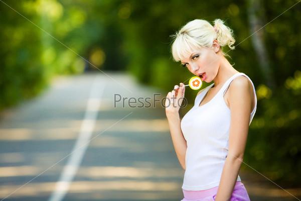 Соблазнительная блондинка стоит с леденцом в руке на фоне дороги