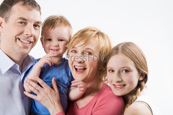 Радостные родители с детьми смотрят в камеру и улыбаются