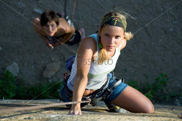 Уверенная альпинистка взбирается на гору