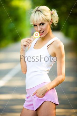 Девушка в майке и шортах стоит на дороге с леденцом в руке