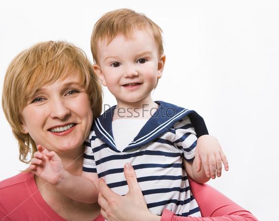 Счастливая женщина держит на руках маленького сына и оба смотрят в камеру
