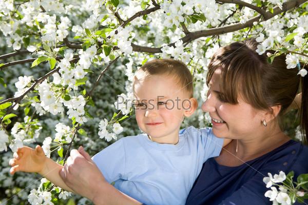Счастливая мама держит сына в цветущем саду