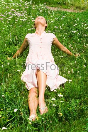 Девушка лежит на зеленой траве с закрытыми глазами и наслаждается летним днем