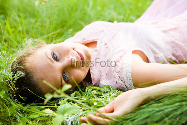 Девушка лежит на траве и смотрит в камеру