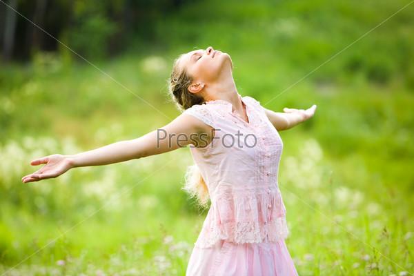 Девушка с закрытыми глазами и раскрытыми руками наслаждается природой