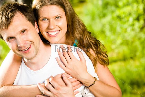 Красивая женщина обнимает своего мужа, они улыбаются и смотрят в камеру
