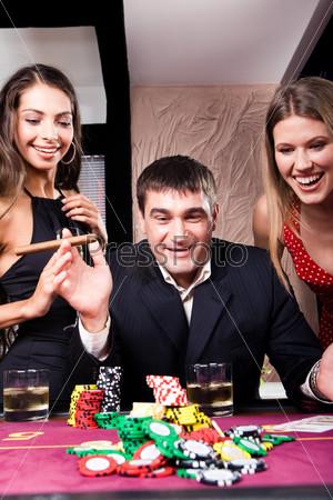 Возбужденный игрок выиграл в казино и радостно смотрит на фишки в окружении двух красивых девушек