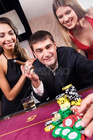 Привлекательный мужчина и две очаровательные девушки смотрят на фишки в казино и улыбаются