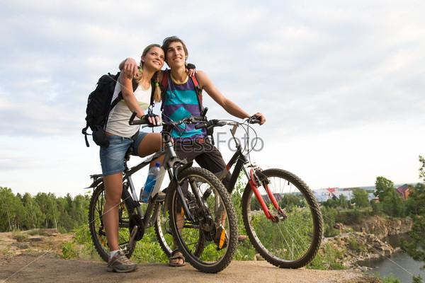 Романтичная пара велосипедистов остановившись смотрит вдаль