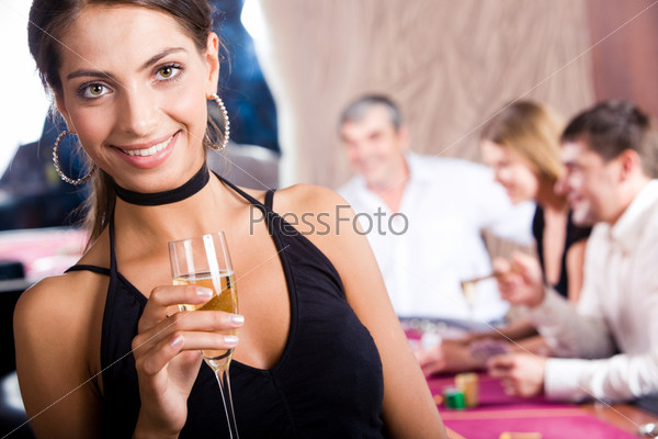 Элегантная брюнетка с бокалом шампанского стоит в казино на фоне игроков за столом