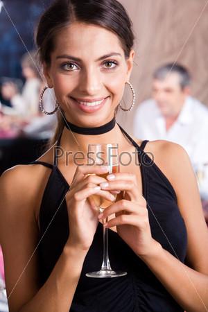 Роскошная девушка в черном платье с бокалом шампанского