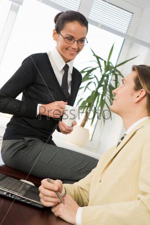 Сотрудники офиса общаются в перерыве за чашкой чая