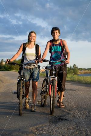 Молодая красивая пара стоит на дороге рядом с велосипедами