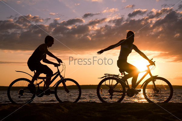 Силуэты двух велосипедистов в лучах заходящего солнца