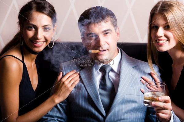 Богатый мужчина с сигарой в окружении очаровательных девушек
