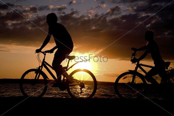 Силуэты велосипедистов на фоне заходящего солнца
