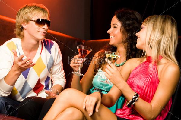Две девушки и молодой человек держат в руках коктейли и разговаривают в ночном клубе
