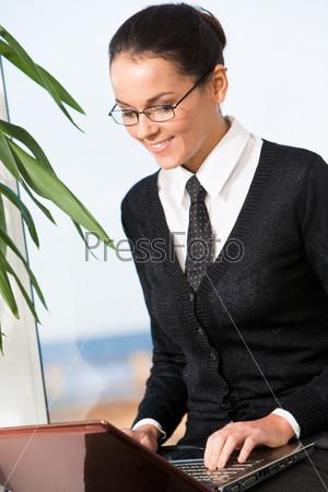 Успешная деловая девушка работает за компьютером в офисе и улыбается