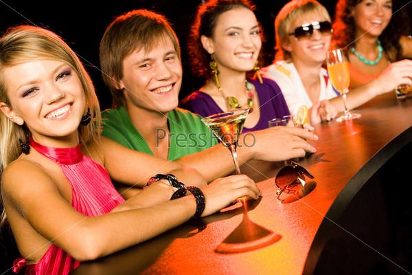 Линия из молодых людей сидит за барной стойкой с коктейлями