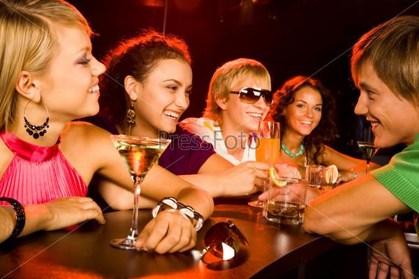Компания молодых людей сидит за барной стойкой и смеется