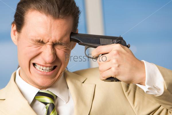 Неудачливый предприниматель зажмурившись держит пистолет у виска