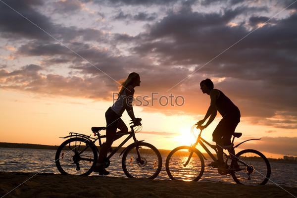 Фотография на тему Девушка и парень на велосипедах на фоне заката на побережье