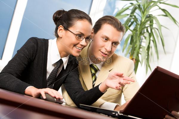 Сотрудники прижавшись друг к другу смотрят в монитор находясь в офисе