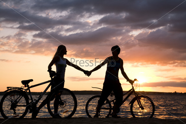 Влюбленная пара идет по побережью с велосипедами, держась за руки