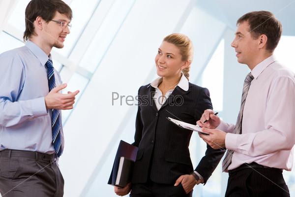 Команда профессионалов стоит и общается в офисе