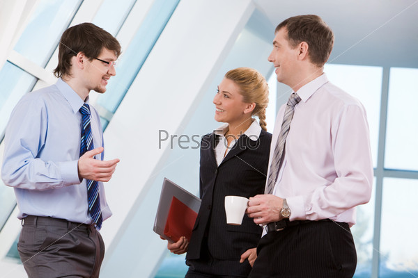 Коллеги обсуждают проект стоя в офисном помещении