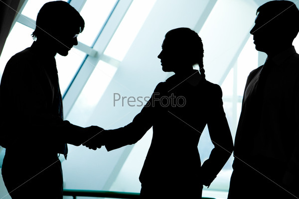 Силуэты деловых людей приветствующих друг друга рукопожатием