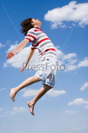 Привлекательный мужчина в воздухе раскинув руки на фоне неба
