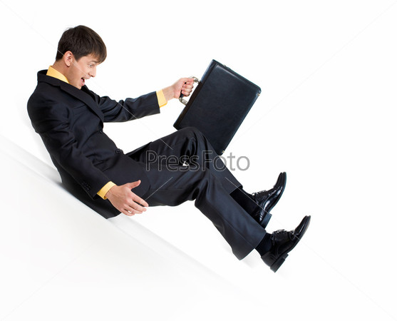 Деловой мужчина скатывается по наклонной плоскости держа в руках портфель