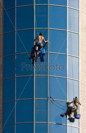 Промышленные альпинисты на стеклянном фасаде здания с инвентарем