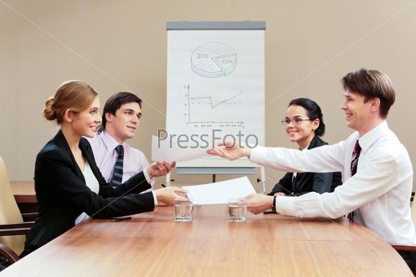 Активное обсуждение рабочего проекта современными сотруднками за столом