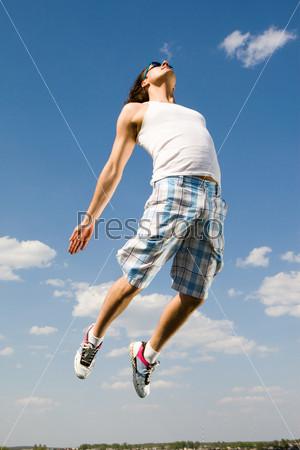 Мускулистый парень прыгает вверх на фоне голубого неба