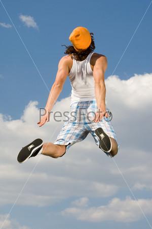 Мускулистый загорелый парень в оранжевой кепке в воздухе спиной к камере