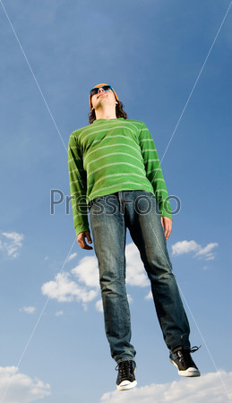 Мужчина в зеленом джемпере и джинсах парит в небе