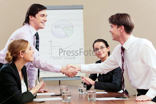 Два бизнесмена пожимают друг другу руки, а женщины одобрительно смотрят сидя за столом