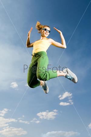 Летящая в воздухе девушка на фоне белых облаков