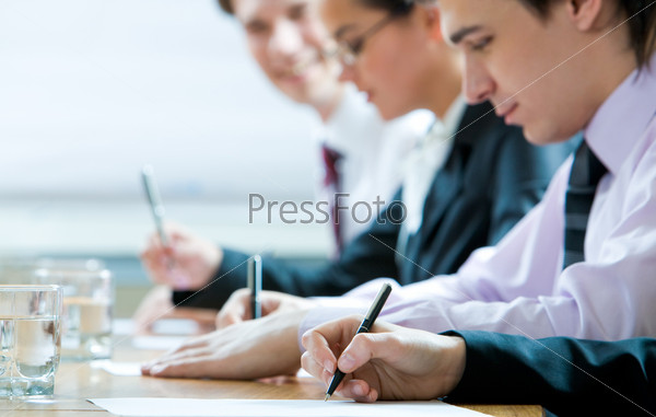 Крупный план руки делающей записи на фоне офисных сотрудников
