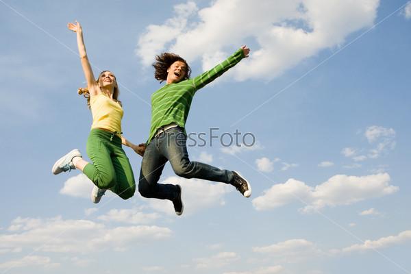 Подпрыгивающая молодая пара смеется держась за руки на фоне неба
