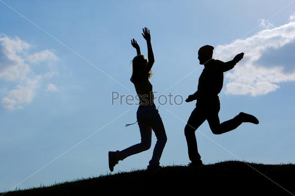 Силуэты двух счастливых людей бегущих навстречу друг другу на фоне природы