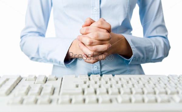 Сцепленные руки менеджера стоящего перед клавиатурой